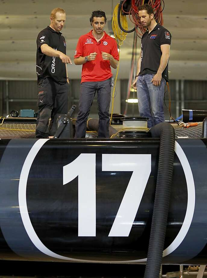 Oracle skipper Jimmy Spithill, left, and Olympic champion Ben Ainslie (right) gave Dario Franchitti (center) a close up view of a 72 foot catamaran Thursday August 15, 2013. Three time IndyCar champion Dario Franchitti received a tour of the Oracle Team USA headquarters in San Francisco, Calif. Photo: Brant Ward, The Chronicle