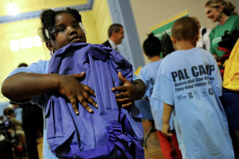 Melani Campbell, 7, receives a backpack filled with school supplies on Thursday, Aug. 15, 2013, at the VI Community Center in Albany , N.Y. Citizens Bank distributed 250 new backpacks and school supplies to elementary school children taking part in the Albany Police Athletic League summer camp program. The initiative is an annual rite of summer for Citizens Bank called Gear for Grades. (Cindy Schultz / Times Union) Photo: Cindy Schultz / 00023521A