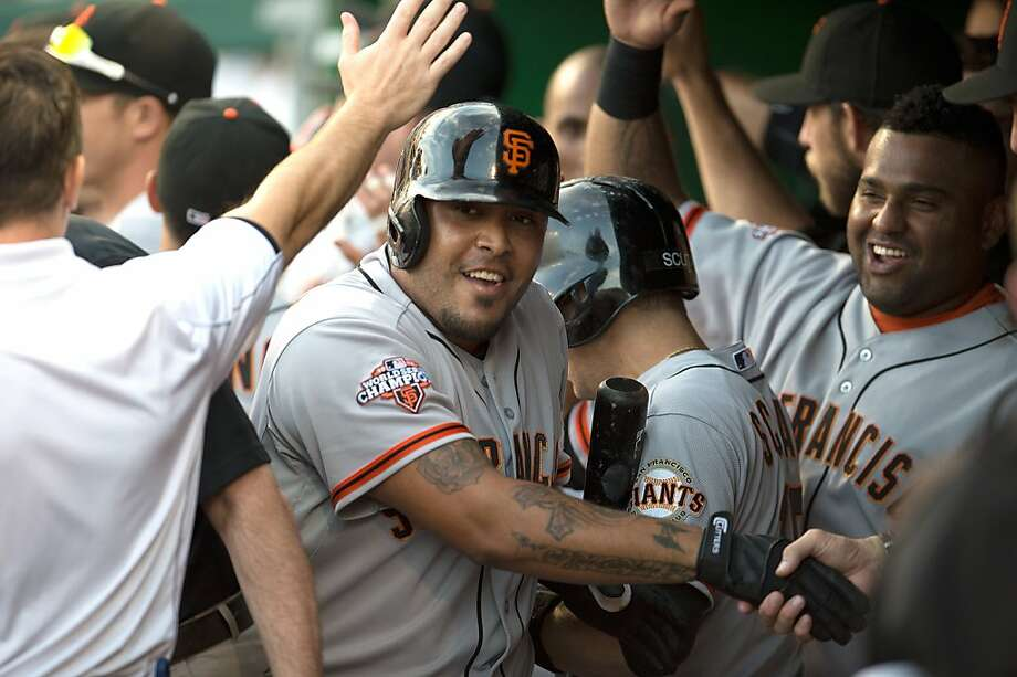 The Giants mob Hector Sanchez after he doubled his season RBI total with a game-winning three-run homer in the ninth. Photo: Harry E. Walker, McClatchy-Tribune News Service