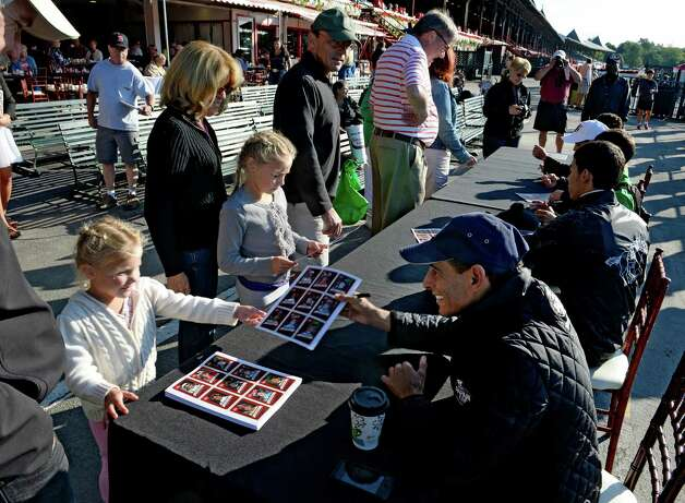 Jockeys, including Hall of Fame member John Velazquez, foreground,  sign their images for patrons on the apron in front of the clubhouse this morning of Aug. 15, 2013 at the Saratoga Race Course in Saratoga Springs, N.Y.   (Skip Dickstein/Times Union) Photo: SKIP DICKSTEIN