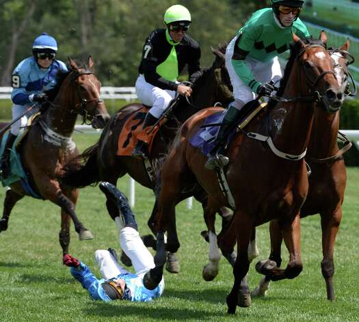 Horses avoid Jockey Darren Nagle after Nagle fell after Total Command stumbled at the second fence of a two and three-eights mile steeplechase Thursday afternoon, Aug. 15, 2013, at  Saratoga Race Course in Saratoga Springs, N.Y.  Horse and rider were fine after the misstep.   (Skip Dickstein/Times Union) Photo: SKIP DICKSTEIN