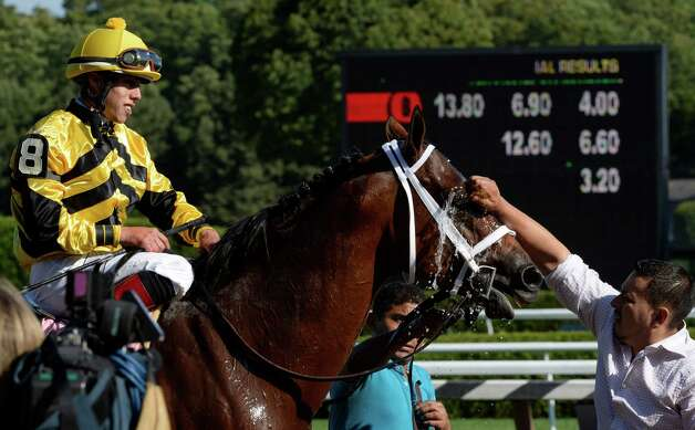Hangover Kid gets a cooling sponge of water as jockey Irad Ortiz Jr. watches after winning the 34th running of The West Point  Aug. 15, 2013 at the Saratoga Race Course in Saratoga Springs, N.Y. The tote board in the background shows the payouts for the race.   (Skip Dickstein/Times Union) Photo: SKIP DICKSTEIN