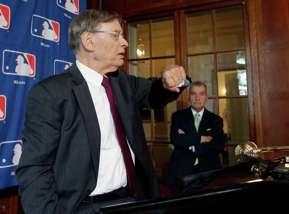 Major League Baseball Commissioner Bud Selig checks his watch before a news conference following baseball meetings at the Otesaga Hotel on Thursday, Aug. 15, 2013, in Cooperstown, N.Y. Atlanta Braves President John Schuerholz stands at right. (AP Photo/Mike Groll) ORG XMIT: NYMG105 Photo: Mike Groll / AP