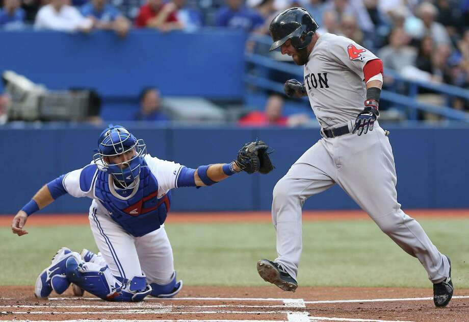 TORONTO, CANADA - AUGUST 15: Dustin Pedroia #15 of the Boston Red Sox is tagged out in the first inning at home plate during MLB game action as J.P. Arencibia #9 of the Toronto Blue Jays reaches to tag him on August 15, 2013 at Rogers Centre in Toronto, Ontario, Canada. (Photo by Tom Szczerbowski/Getty Images) ORG XMIT: 163495018 Photo: Tom Szczerbowski / 2013 Getty Images