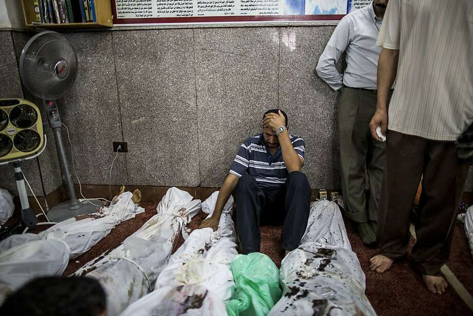A man mourns over the body of a relative at the El-Iman mosque, where the bodies of pro-Morsi protesters who were killed in Wednesday's government crackdown were brought for identification, in the Nasr City district of Cairo, Aug. 15, 2013. The death toll from Egypt's bloody crackdown on supporters of ousted President Mohammed Morsi soared beyond 500 Thursday, with more than 3,700 people injured, the Health Ministry said. (Bryan Denton/The New York Times) Photo: Bryan Denton, New York Times