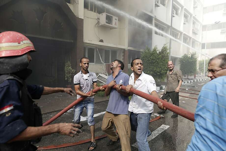 Egyptian civilians help firefighters to battle flames at the Giza governorate building that was stormed and torched by angry supporters of Egypt's ousted president, Cairo, Egypt, Thursday, Aug. 15, 2013. Egypt faced a new phase of uncertainty on Thursday after the bloodiest day since its Arab Spring began, with hundreds of people reported killed and thousands injured as police smashed two protest camps of supporters of the deposed Islamist president. Wednesday's raids touched off day-long street violence that prompted the military-backed interim leaders to impose a state of emergency and curfew, and drew widespread condemnation from the Muslim world and the West, including the United States. (AP Photo/Hassan Ammar) Photo: Hassan Ammar, Associated Press