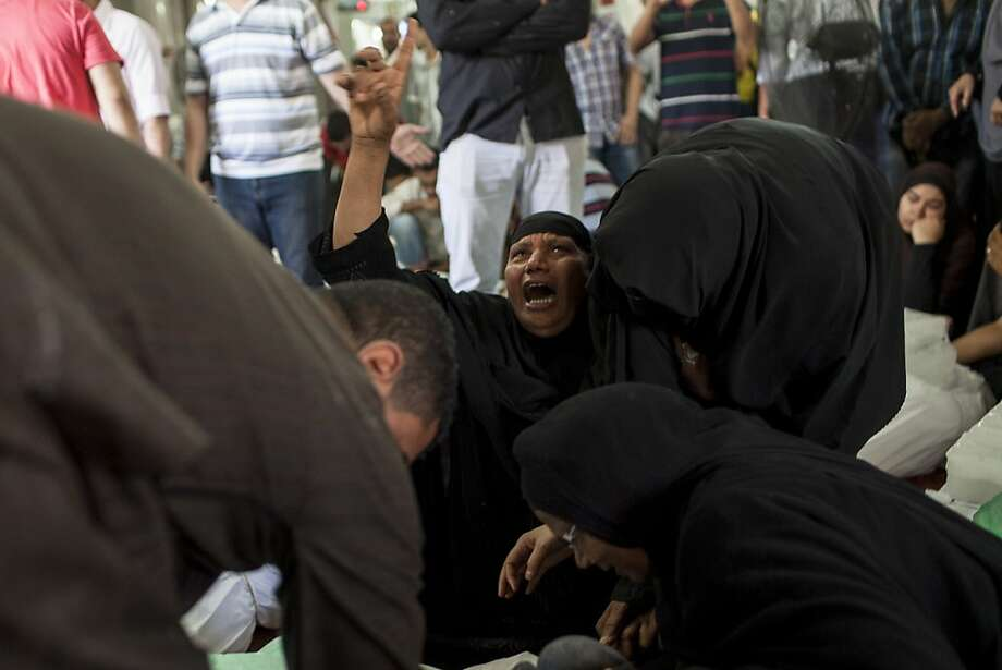 CAIRO, EGYPT - AUGUST 15:  An Egyptian woman identifies the body of a family member, a supporter of deposed Egyptian President Mohammed Morsi killed during a violent crackdown by Egyptian Security Forces on pro-Morsi sit-in demonstrations the day before, at the al-Iman Mosque in Nasr City on August 15, 2013 in Cairo, Egypt.  An unknown number of pro-Morsi protesters were killed in Egypt's capital yesterday as Egyptian Security Forces undertook a planned operation to clear Morsi supporters from two sit-in demonstrations in Cairo where they have camped for over one month. Egyptian Police and Army forces entered protest sites in the Nasr City and Giza districts at dawn on August 14, using tear gas, live fire and bulldozers to disperse protesters and destroy the camps. A state of emergency has been declared in Egypt that began yesterday afternoon and will last for one month. (Photo by Ed Giles/Getty Images) Photo: Ed Giles, Getty Images