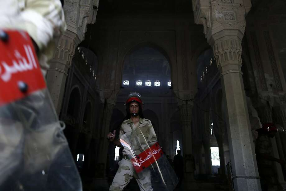 Egyptian Army soldiers walk among the charred remains of the Rabaah al-Adawiya mosque, in the center of the largest protest camp of supporters of ousted President Mohammed Morsi, that was cleared by security forces, in the district of Nasr City, Cairo, Egypt, Thursday, Aug. 15, 2013. Egypt faced a new phase of uncertainty on Thursday after the bloodiest day since its Arab Spring began, with hundreds of people reported killed and thousands injured as police smashed two protest camps of supporters of the deposed Islamist president. Wednesday's raids touched off day-long street violence that prompted the military-backed interim leaders to impose a state of emergency and curfew, and drew widespread condemnation from the Muslim world and the West, including the United States. (AP Photo/Hassan Ammar) Photo: Hassan Ammar, Associated Press