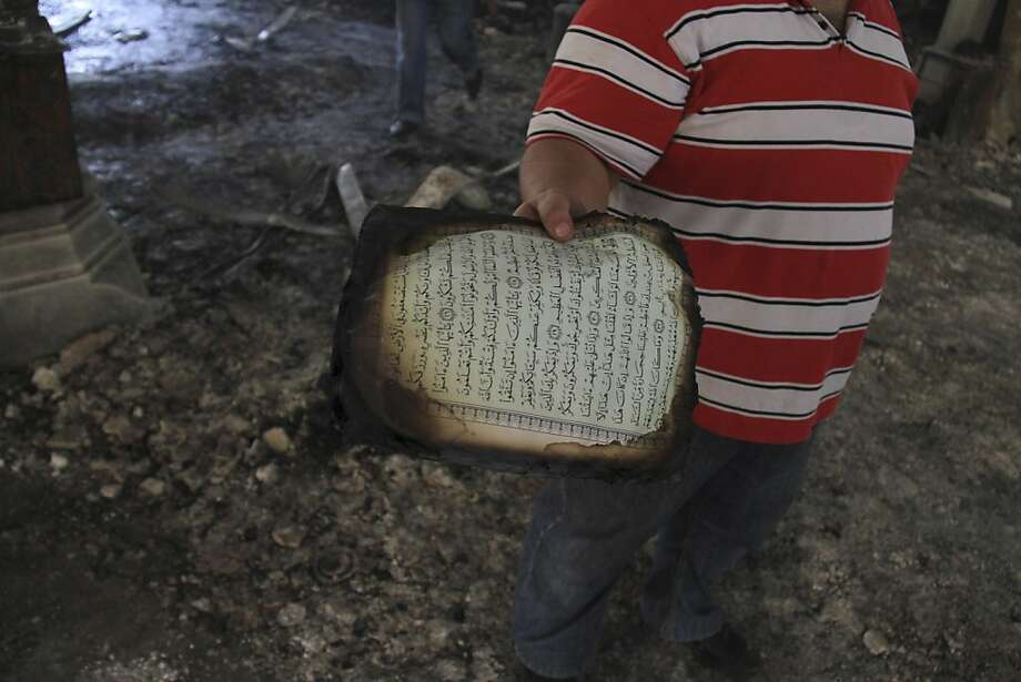 An Egyptian holds a burned page form the Quran walk among the burned remains of the Rabaah al-Adawiya mosque, in the center of the largest protest camp of supporters of ousted President Mohammed Morsi, that was cleared by security forces, in the district of Nasr city, Cairo, Egypt, Thursday, Aug. 15, 2013. The death toll keeps going up in Egypt after security forces swept through two sit-in sites yesterday, operated by supporters of Morsi. An Egyptian Health Ministry spokesman now says hundreds of people died in the violence that has prompted international criticism. (AP Photo/Ahmed Gomaa) Photo: Ahmed Gomaa, Associated Press