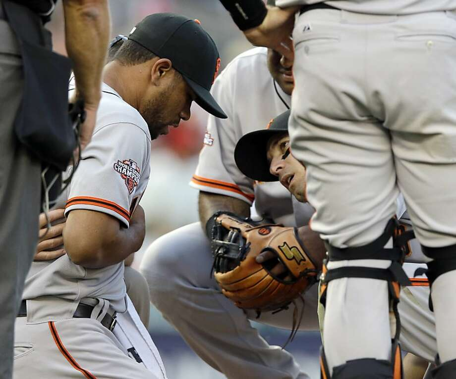 San Francisco Giants relief pitcher Sandy Rosario, left, is surrounded by teammates after being hit by a ball off the bat of Washington Nationals' Adam LaRoche during the seventh inning of a baseball game at Nationals Park Thursday, Aug. 15, 2013, in Washington. Rosario left the game. The Giants won 4-3. (AP Photo/Alex Brandon) Photo: Alex Brandon, Associated Press