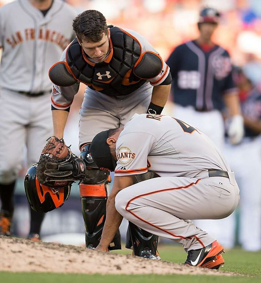 San Francisco Giants relief pitcher Sandy Rosario (43) is checked on by teammate Buster Posey (28) after being hit in the chest by a line drive ball off the bat of Washington Nationals first baseman Adam LaRoche (25) during the seventh inning at Nationals Park in Washington, D.C, Thursday, August 15, 2013. San Francisco defeated Washington 4-3. (Harry E. Walker/MCT) Photo: Harry E. Walker, McClatchy-Tribune News Service