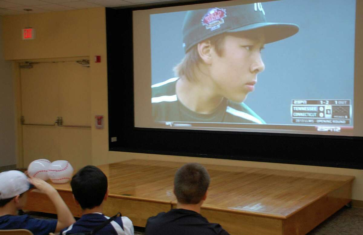 Westport Little League pitcher Chad Knight looms large on the big-screen television at the Westport Library as local fans cheered their home team on to victory Thursday night.