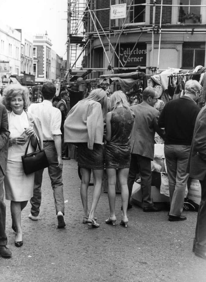 Circa 1965:  Two young women wearing miniskirts at Portobello Market, Kensington, London. Photo: Central Press, Getty Images
