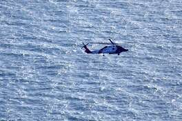 A Coast Guard helicopter flies over the area of an explosion and fire on the oil platform in the Gulf of Mexico. Four people were transported to a hospital with critical burns and two were missing.