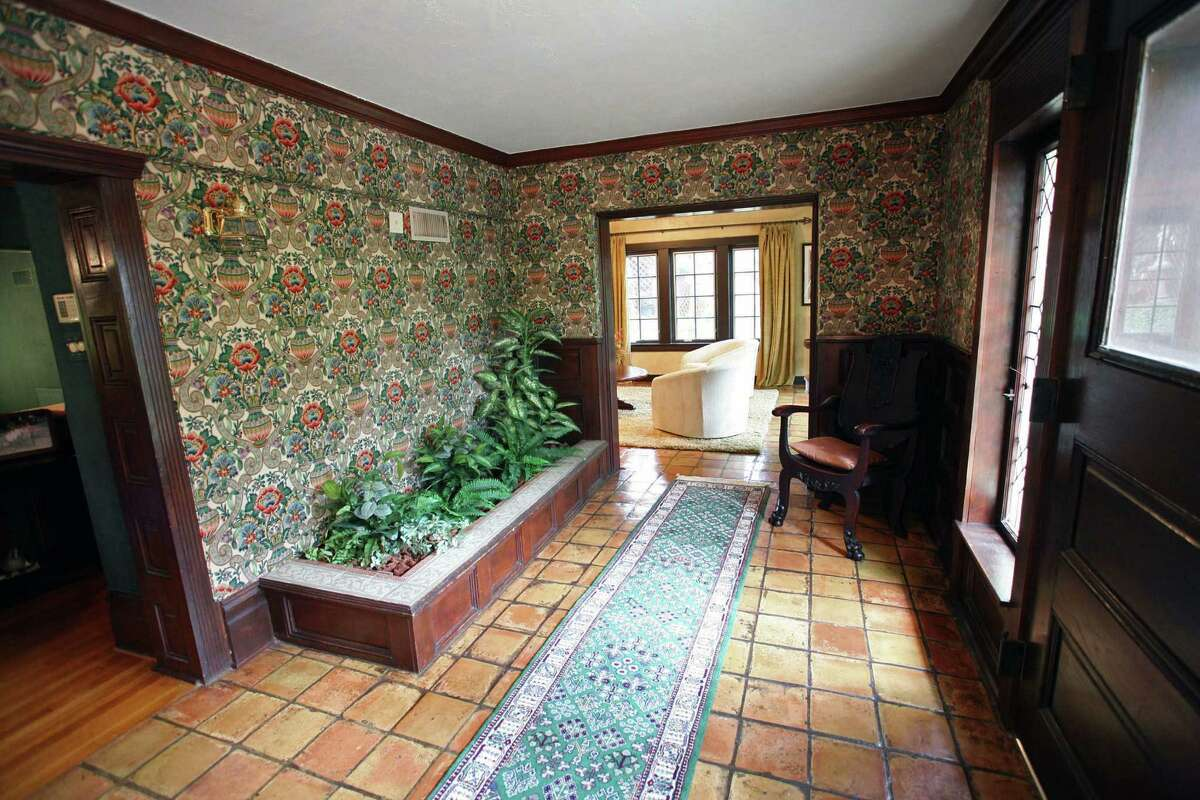 The walls of the entry are covered in a fabric that looks like wallpaper.