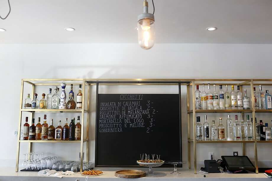 Pesce's sleek bar features a lineup of ready-made cicchetti described on the chalkboard, above, with choices like a shot of melon with prosciutto, left. Photo: Ian C. Bates, The Chronicle