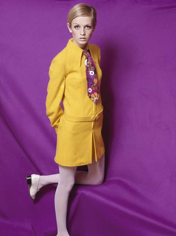 A portrait of the model Twiggy wearing a fashionable yellow collared outfit with a multi-colored floral tie, posing for the camera in a studio against a brightly colored purple backdrop  in 1967. Photo: Popperfoto, Popperfoto/Getty Images