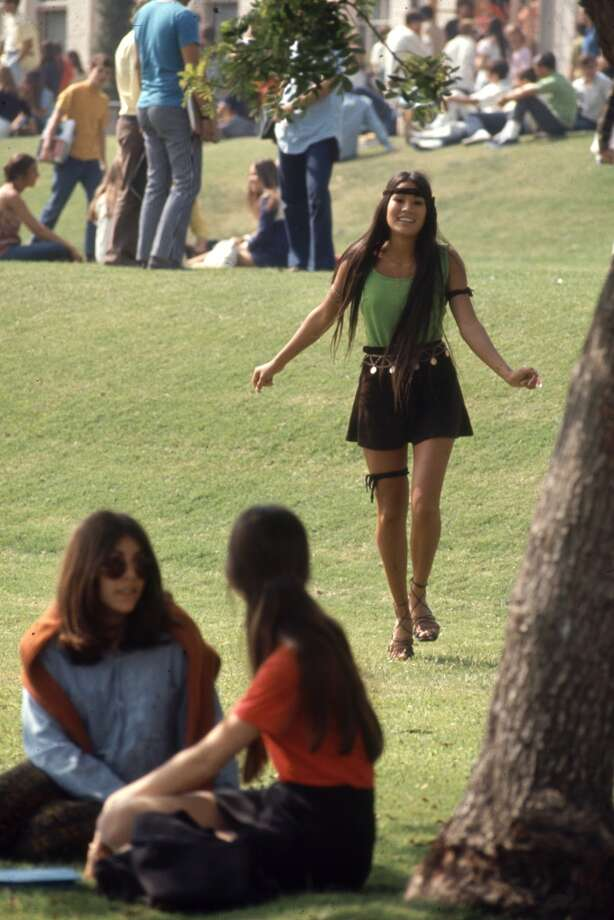 View of a Southern California high school student as she walks on the grass dressed in a green tanktop and a miniskirt, accented with a headband, armband, and a thighband, October 1969. Photo: Arthur Schatz, Time & Life Pictures/Getty Image