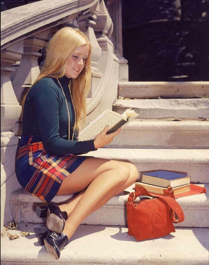 A female college student wearing a plaid miniskirt sits on a flight of steps and studies her textbook, early 1970s. Photo: Lambert, Getty Images
