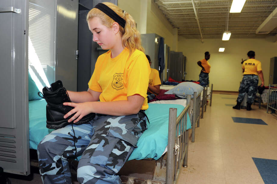 Hannah Laflin, 14, of Trumbull, laces her boots during a break in the barracks at Camp Niantic, during summer boot camp for the student cadets from the Bridgeport Military Academy, in Niantic, Conn., Aug. 15, 2013. Photo: Ned Gerard / Connecticut Post