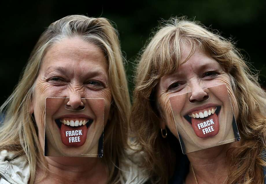 "Tongue and cheek: Anti-fracking activists try to win their foes over with clip-on smiles while demonstrating near the Cuadrilla exploratory drilling site in Balcombe, England. The protesters set up a six-day ""Reclaim the Power"" camp outside the village. Photo: Gareth Fuller, Associated Press"