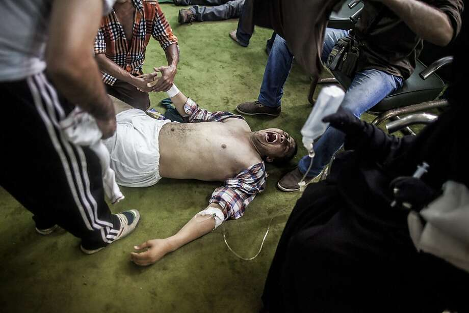 A pro-Morsi demonstrator wounded by gunfire is assisted by medical personnel at Al-Nour Mosque on Cairo's Ramses Square. Photo: Bryan Denton, New York Times