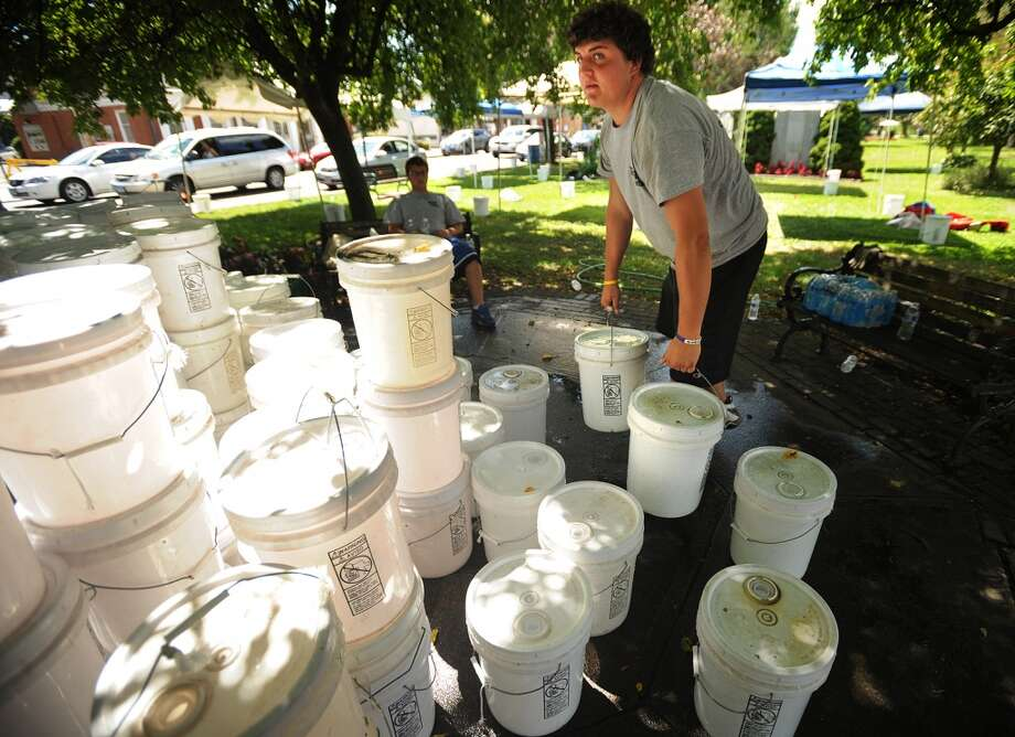 Billy Varnum, of Milford, carries buckets of water to anchor canopies for Saturday's Milford Oyster Festival on the Milford Green on Thursday, Aug. 15, 2013. The festival runs from 10 a.m. to 6 p.m. on Saturday, Aug. 16, 2013 in Milford, Conn., and features a performance by Blues Traveler. Photo: Brian A. Pounds
