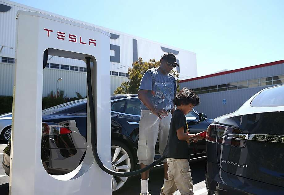 FREMONT, CA - AUGUST 16:  Jinyao Desandies (R) and Dandre Desandies (L) plug the Tesla Supercharger into their Tesla Model S sedan outside of the Tesla Factory on August 16, 2013 in Fremont, California. Tesla Motors opened a new Supercharger station with four stalls for public use at their factory in Fremont, California. The Superchargers allow owners of the Tesla Model S to charge their vehicles in 20 to 30 minutes for free. There are now 18 charging stations in the U.S. with plans to open more in the near future.  (Photo by Justin Sullivan/Getty Images) Photo: Justin Sullivan, Getty Images