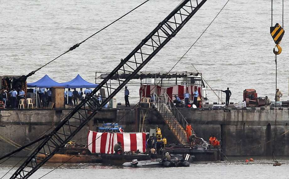 Navy divers stand around the 16-year-old diesel-powered, Russian-made submarine INS Sindhurakshak, covered with a red and white sheet, at the Naval Dockyard in Mumbai, India, Friday, Aug. 16, 2013. Indian navy divers on Friday recovered four severely burned bodies of sailors who had been trapped inside the submarine damaged by twin explosions, officials said. The navy said it was doubtful that any of the other 14 sailors aboard survived. Photo: Rajanish Kakade, Associated Press