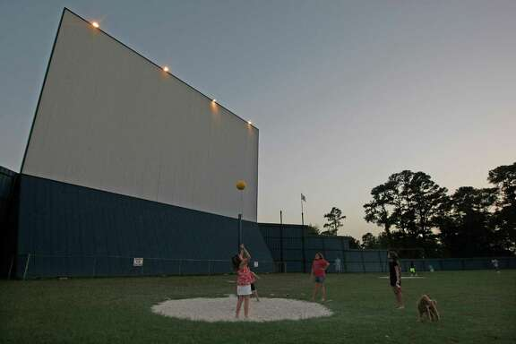 Children play near the outdoor screen before the movie at The Showboat Drive-in Thursday, Aug. 8, 2013, in Hockley. ( Johnny Hanson / Houston Chronicle )