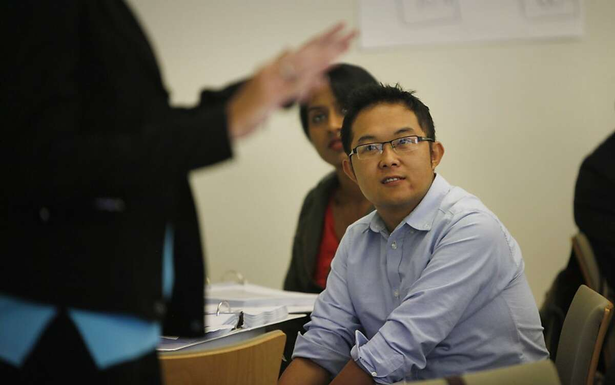 Brian Li (right) of Alameda and Esha Menon (second from right) of Cupertino listen to Susan Ladua (hands at left), certified trainer representing Covered California lecture during a training session for