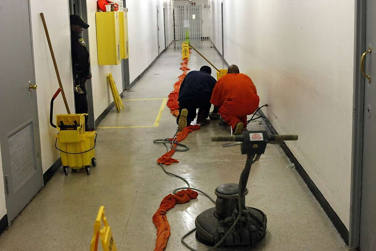 Inmates clean up the flooded hallway from the backed up and worn out plumbing, Monday August 12, 2013, on the 7th floor of the San Francisco County Jail, which is slated to be closed and rebuilt in the near future in San Francisco, Calif.