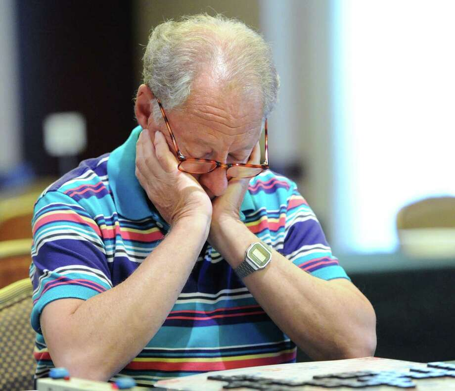 Jack Eichenbaum of Flushing, Queens, New York City, with eyes pointed straight down, looks as if he is sleeping but instead he is studying the board while playing a Scrabble match during the third annual Old Greenwich Scrabble Tournament at the Hyatt Regency Greenwich, Friday, August 16, 2013. Photo: Bob Luckey / Greenwich Time