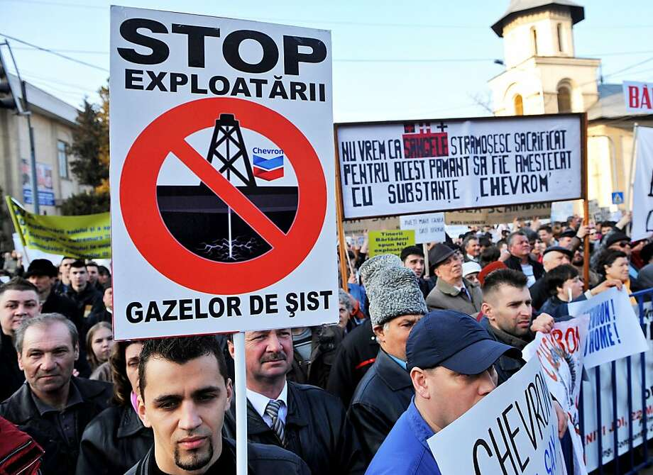 "A Romanian protester holds a banner, ""STOP shale gas exploits,"" during a rally against the shale gas exploration in Barlad, about 150 miles from Bucharest. Chevron has permits to explore for shale gas. Photo: Daniel Mihailescu, AFP/Getty Images"