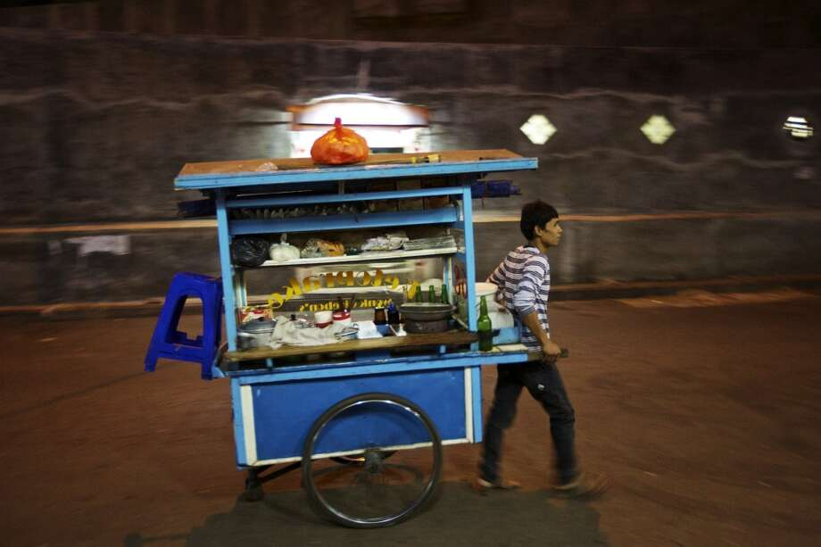 Indonesia: A man wheels his mobile restaurant down a main road in Jakarta. As part of a major effort to  relieve Jakarta's massive traffic problem, the city's government is attempting to relocate Jakarta's traditional street vendors from the crowded roads and into specially designated market locations.  But, not everyone is happy about the plan as local gangs make money on illegal rents charged to the vendors for their spots on public streets and vendors worry their business will be less off the heavily trafficked roads. Photo: Ed Wray, Getty Images