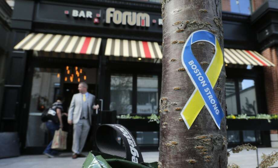 "Massachusetts: A ""Boston Strong"" sticker is stuck to the trunk of a tree as a manager opens the door for a worker outside the Forum restaurant and bar near the finish line of the Boston Marathon.  The restaurant, which was damaged after one of the bombs exploded in front of the building, reopened Thursday, for a private event, for the first time since the race. Photo: Charles Krupa, Associated Press"