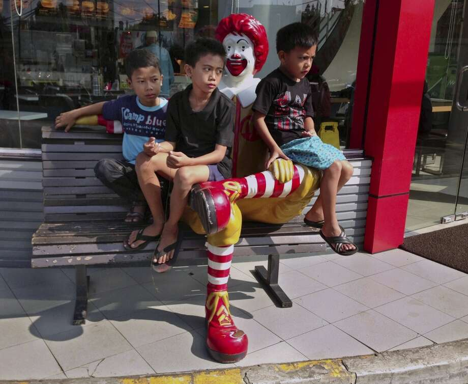 Indonesia: Kids sit on a Ronald McDonald statue at a McDonald's restaurant in Bandung, West Java, Indonesia. Photo: Dita Alangkara, Associated Press