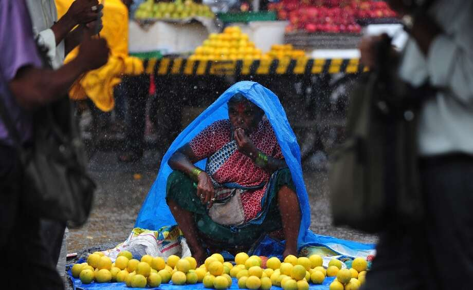 India: A fruit seller chews an apple as she waits for customers during heavy rains in Mumbai. The monsoon season, which runs from June to September, accounts for about 80 percent of India's annual rainfall, vital for a farm economy which lacks adequate irrigation facilities. However, the flooding also causes hundreds of deaths and damage to infrastructure, homes and farms across India. Photo: Indranil Mukherjee, AFP/Getty Images