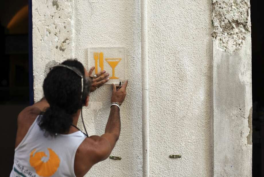 Portugal: Brazilian designer Jorge Franco places a restaurant symbol board outside a bar which is to be opened at Lisbon's Cais Sodre port area,. Marco Silva, who is the owner of the bar and has been working in the hotel industry in Lisbon for ten years, said he decided to open his own business because he believes the tourist sector is growing in that area of the city. Photo: Francisco Seco, Associated Press