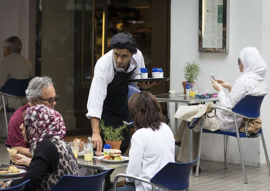 UK: A waiter serves customers their food at an outdoor restaurant terrace in St Christopher's Place in London. U.K. services growth accelerated more than economists forecast last month to the fastest pace in more than six years, adding to evidence Britain's economic recovery is gathering momentum. Photo: Simon Dawson, Bloomberg