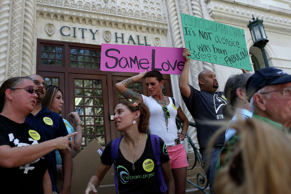 Andrea Moutria, left/center, and Alberto Barragan, right/center, get into place with signs for members of the Community Alliance for a United San Antonio to speak about the recording of District 9 City Councilwoman Elisa Chan's comments about homosexuality at City Hall in San Antonio on Friday, August 16, 2013.