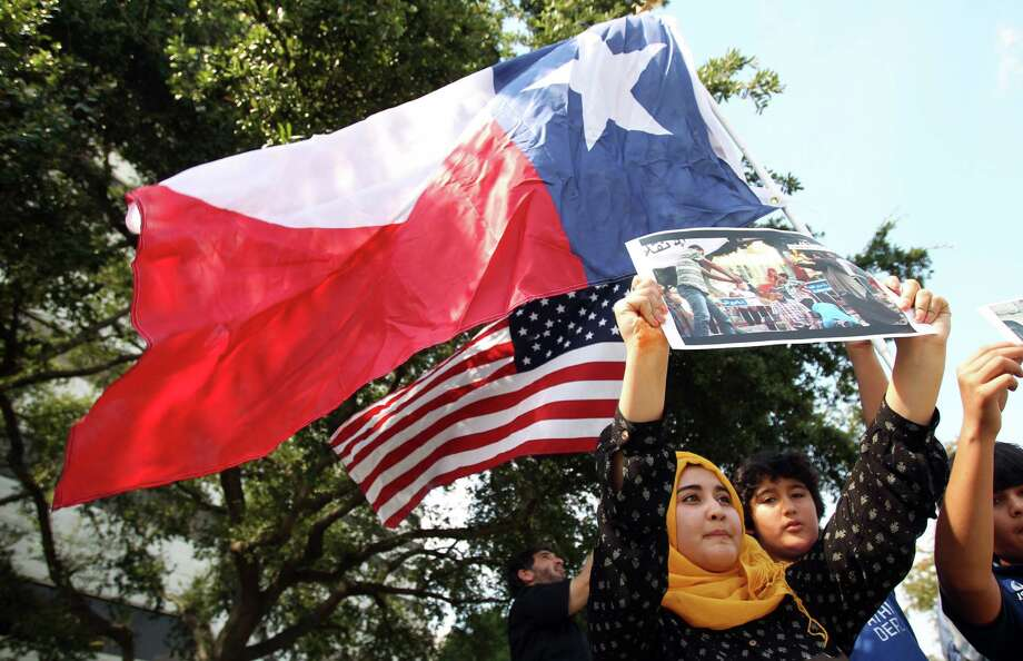 Marium Khan, 17, holds photographs of violent scenes in Egypt as the Muslim American Society protest outside the Egyptian Consulate to condemn the violence in Egypt, and call upon international community to restore democratic process and immediately halt assault on peaceful protestors on Friday, Aug. 16, 2013, in Houston. Photo: Mayra Beltran, Houston Chronicle / © 2013 Houston Chronicle