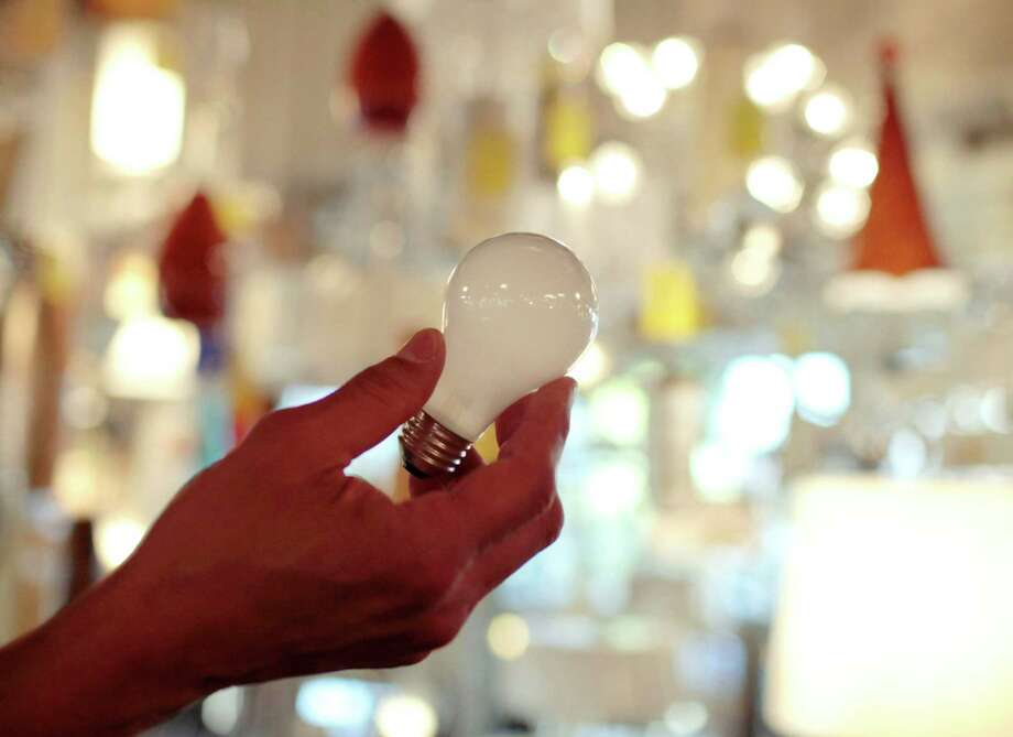 FILE - In this Jan. 21, 2011, file photo, Manager Nick Reynoza holds a 100-watt incandescent light bulb at Royal Lighting in Los Angeles. In the U.S., companies have different motivations for offering innovative electricity plans. Traditional regulated utilities are trying to reduce stresses on their grids. Upstart power providers are trying to lure new customers.  (AP Photo/Jae C. Hong, File) ORG XMIT: NYBZ401 Photo: Jae C. Hong / AP