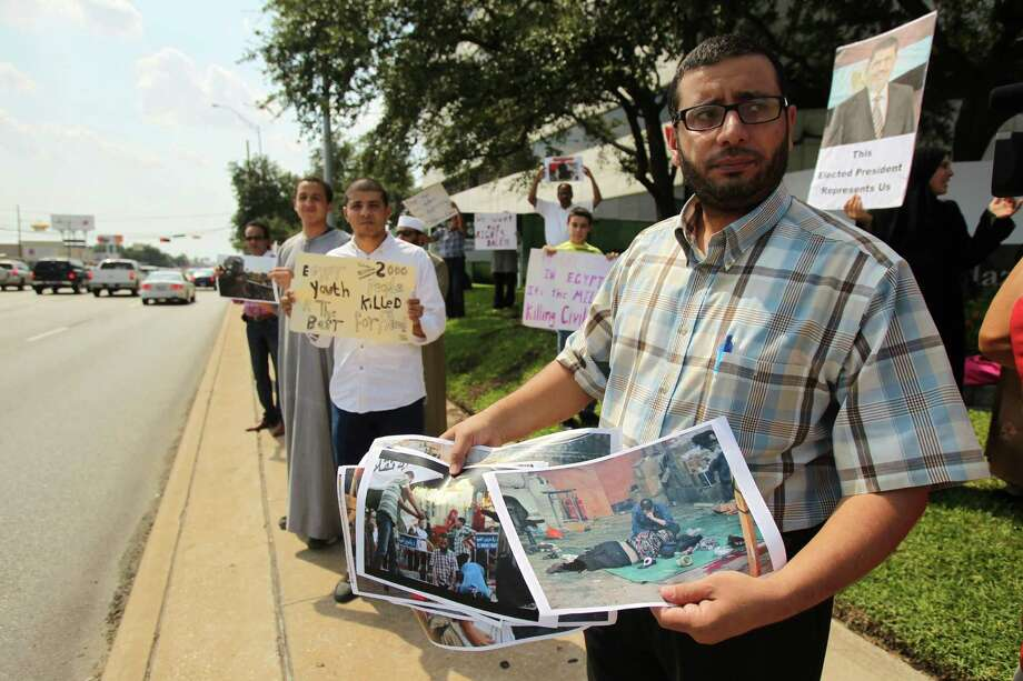 """We are here to support democracy and human rights"" says Wahed Wasel while holding graphic photographs as he joins the Muslim American Society protest outside the Egyptian Consulate to condemn the violence in Egypt, and call upon international community to restore democratic process and immediately halt assault on peaceful protestors on Friday, Aug. 16, 2013, in Houston. Photo: Mayra Beltran, Houston Chronicle / © 2013 Houston Chronicle"