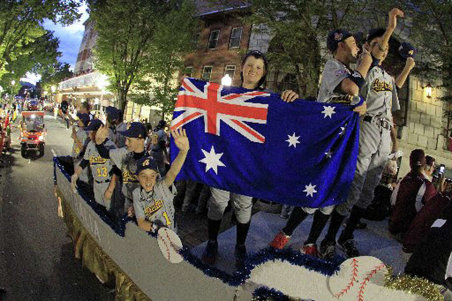 Players from Perth, Australia, display their nation's flag during the Grand Slam Parade in downtown Williamsport, Pa. Wednesday evening. Perth is the first Australian team ever to play in the Little League World Series. Photo: Associated Press / Associated Press