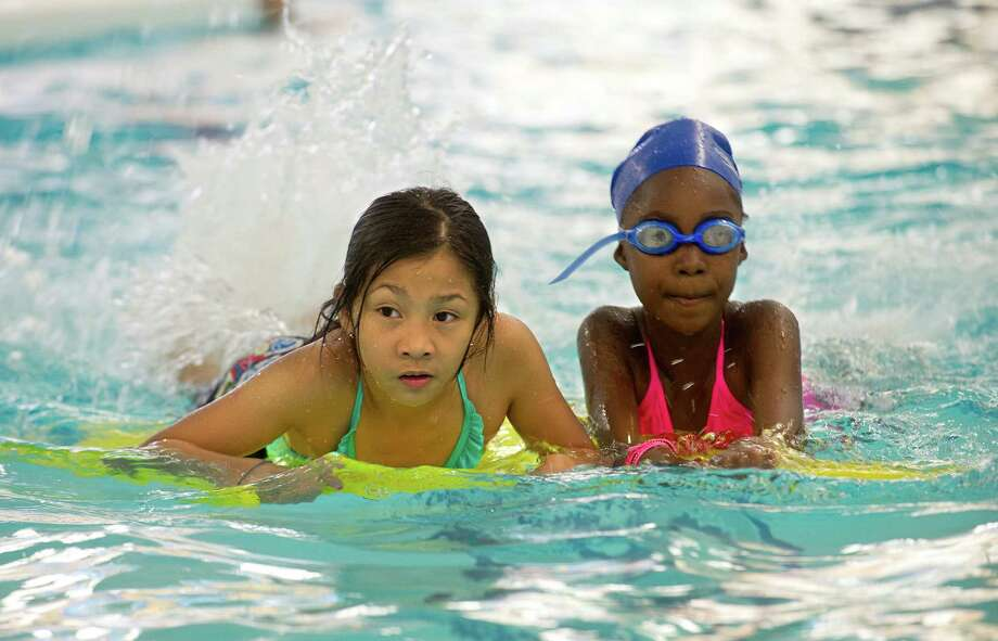 Elizabeth Ines, 9, left, and Jamaish Tilus, 9, right, practice kicking during a swimming class at the Stamford YMCA on Thursday, August 15, 2013. Photo: Lindsay Perry / Stamford Advocate