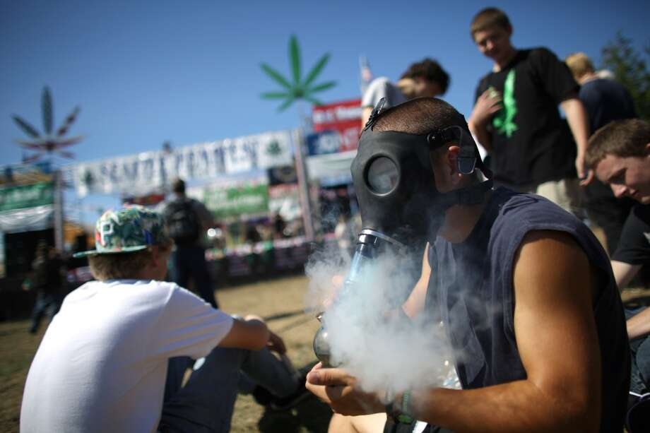 A man uses a gas mask to smoke marijuana during the first day of Seattle's annual Hempfest at Myrtle Edwards Park on Friday, August 16, 2013. Photo: JOSHUA TRUJILLO, SEATTLEPI.COM