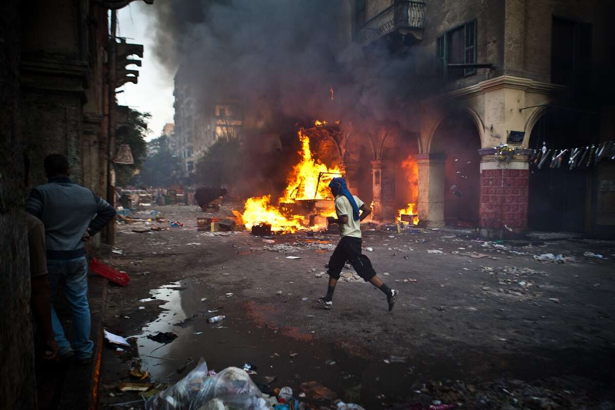 A supporter of the Muslim Brotherhood and of ousted president Mohamed Morsi runs past a burning vehicle during clashes with security officers close to Cairo's Ramses Square, on August 16, 2013. Backers of Egypt's ousted president pledged to stage daily demonstrations as they ended a day of angry protests in which at least 75 people were killed during the day. AFP PHOTO / VIRGNIE NGUYEN HOANGVIRGINIE NGUYEN HOANG/AFP/Getty Images