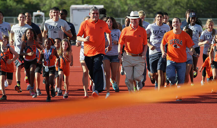 UTSA President Ricardo Romo (center) and Bexar County Judge Nelson Wolff (right of Romo) lead a group to run toward a finish line during the opening ceremonies for the new UTSA Track & Field Stadium off of Loop 1604 and Kyle Seale Parkway on Friday, Aug. 16, 2013. Guests were also treated to an exhibition soccer match between UTSA and the University of the Incarnate Word women's soccer teams.