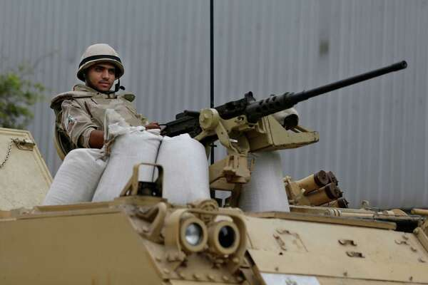 """An Egyptian Army soldier takes his position on top of an armored vehicle while guarding an entrance to Tahrir Square, in Cairo, Egypt, Friday, Aug. 16, 2013. Egypt is bracing for more violence after the Muslim Brotherhood called for nationwide marches after Friday prayers and a """"day of rage"""" to denounce this week's unprecedented bloodshed in the security forces' assault on the supporters of the country's ousted Islamist president that left many hundred dead. (AP Photo/Hassan Ammar)"""